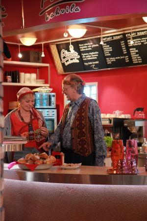 Ainon kahvilan 60-luku bileissä. Aino ja Ensio seisovat tiskin takana. Aino hymyilee.