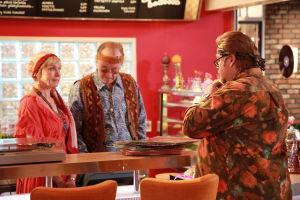 Ainon kahvilan 60-luku bileissä. Aino ja Ensio seisovat tiskin takana. Asiakas seisoo tiskin edessä.