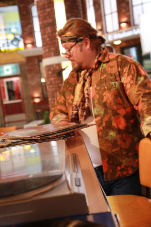 Ainon kahvila 60-luku bileet. Mies tiskillä. Edessä levysoitin ja vinyylilevyjä.