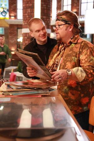Ainon kahvila 60-luku bileet. Kaksi miestä tiskillä. Toinen pitelee vinyylilevyjä kädessään.
