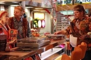 Ainon kahvilan 60-luku bileet. Ensio ja Aino tiskin takana. Tiskin edessä mies selailee vinyylilevyjä.