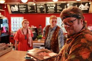 Ainon kahvila 60-luku bileet. Ensio ja Aino tiskin takana. Asiakas tiskin edessä katsoo kameraan.