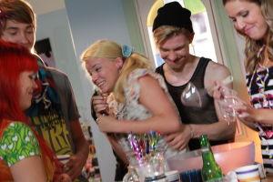 Emmin synttäribileet. Cicca, Rasmus, Vilma, Karri ja Krista pöydän ympärillä. Vilma pitää kaksin käsin pullosta kiinni.