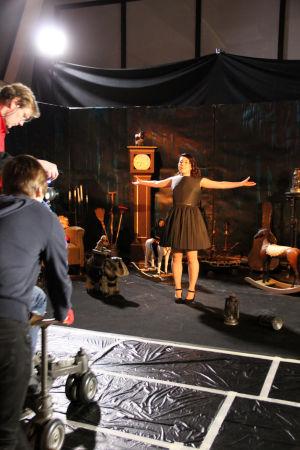 Emmi musavideon lavasteissa musta mekko päällään. Tiimiä edessä.