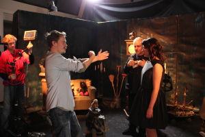 Ohjaaja ohjaa Emmiä musiikkivideon lavasteissa. Taustalla tiimiä.