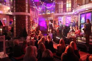 Bändi soittamassa. Yleisöä lattialla ja rappusilla.