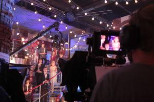 Ihmisiä laulamassa portailla kynttilät käsissään. Edessä kamera ja kameramies.