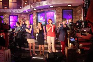 Marika, Elina, Lissu ja Aapo laulamassa. Edessä kamera.