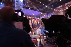 Ihmisiä laulamassa rappusilla. Edessä kaksi kameraa.