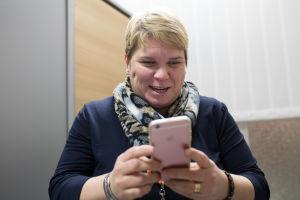 Katja Kuusela esittelee hymyillen älypuhelimensa ominaisuuksia.