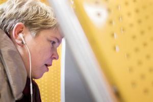 Katja Kuusela kuulokkeet korvillaan pankkiautomaatilla.