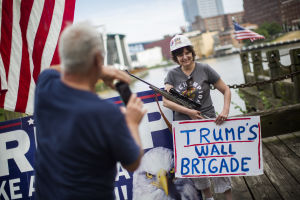 """En kvinna som stöder Trump poserar med hjälm, gevär tillsammans och skylten """"Trumps murbrigad""""."""