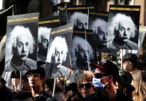 Demonstranter bär skyltar med Albert Einsteins bild och texten flyktingar är välkomna.