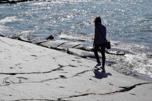 En siluett av en person som går längs klippkanten mot vattnet vid föboda i Jakobstad.