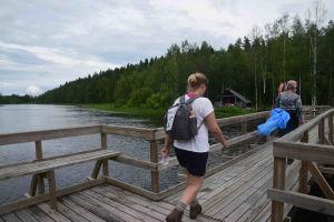 Bockabron i Kiisk i Pedersöre. Två personer med ryggsäckar och gummistövlar går över den smala träbron.