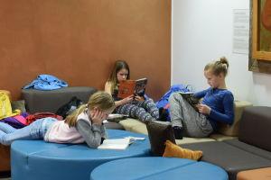 Tre barn sitter och ligger på en soffa och läser