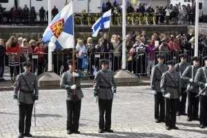 Försvarsmaktens representanter står med Finlands statsflagga på Salutorget i Helsingfors.