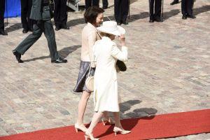 Drottning Sonja av Norge och fru Jenni Haukio går på röda mattan utanför presidentslottet.