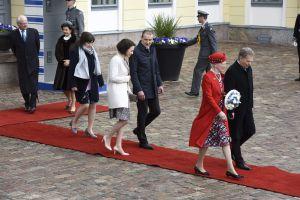 De nordiska kungligheterna promenerar ut från presidentens slott på röda mattan.