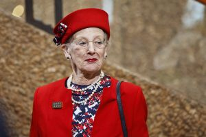 Närbild av drottning Margrethe II av Danmark iklädd röd dräkt och röd hatt då hon småler.