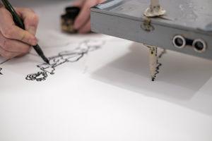 Piirustusrobotti ja ihminen piirtävät yhtä aikaa paperille.