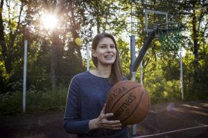 Ung kvinna med blå tröja i närbild. Hon håller i en basketboll.