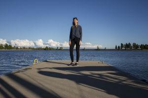 Sara Jakobsén står längst ute på en bygga med ansiktet vänt mot kameran.