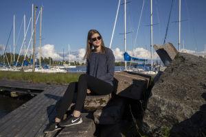 Sara Jakobsén sitter på en brygga. Hon har blå tröja och svarta byxor. I bakgrunden syns segelbåtar.
