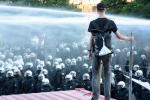 En demonstrant står uppe på en container och blickar ner på kravallpoliser. Över polisernas huvuden syns vattenkanoner.