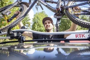 Matti Lehikoinen nostaa maastopyörää auton katolle.