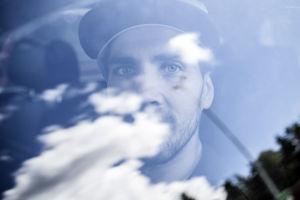Matti Lehikoinen istuu autossaan, auton ikkunasta heijastuu pilviä.