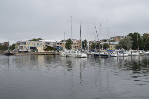 En småbåtshamn med segelbåtar. I bakgrunden skymtar ett nybyggt flervåningshus.