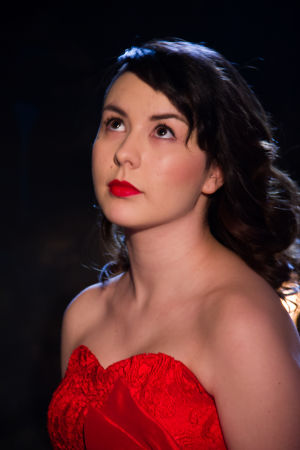 Emmi punaisessa mekossa ja punaisissa huulissa.