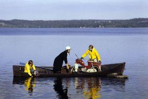 Järjestäjä Juha Hyvönen, näyttelijä Erkki Siltola ja tunnistamaton kuvausryhmän jäsen mopedin kanssa veneessä Tankki täyteen -sarjan kuvauksissa.