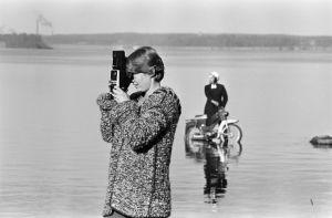 Tunnistamaton valokuvaaja työssä, taustalla näyttelijä Erkki Siltola mopedin kanssa vedessä Tankki täyteen -sarjan kuvauksissa.
