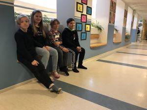 Elever sitter i skolans korridor.