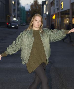 Sanna Helander tar ett danssteg. Håller ut händerna.