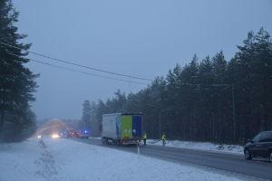En snöig väg där det står olycksfordon med blåljusen på.