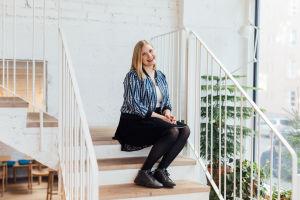 Michaela von Kugelgen sitter i en trappa. Väggen bakom är vit och trappan är också vit, med trappräcke av metall. Hon har på sig en svart kjol och en blåspräcklig jacka.