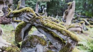 Staty ligger på rygg och håller i sina fötter. I bakgrunden statyer i jogaställning.