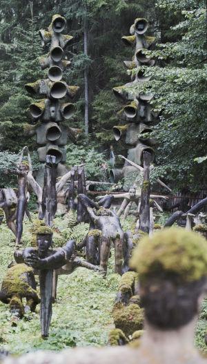 Sammaloituneita betonipatsaita jooga-asennoissa metsän keskellä.