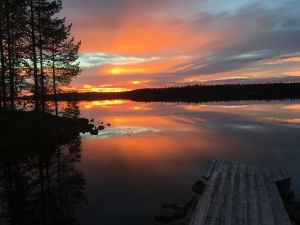 Oranssihehkuinen auringonlasku Suomusjärven Kianta-järvellä.