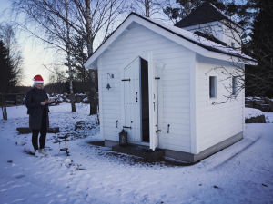 Hyvin pieni, valkoiseksi maalattu kirkko, lunta maassa. Vieressä seisoo mustiin pukeutunut nainen, jolla punainen tonttulakki päässä.