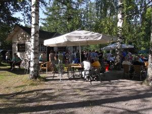 Ihmisiä terassilla, pitkä jono pieneen puutaloon jossa myydään jäätelöä.