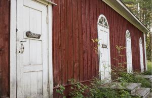 Varjakansaaren vanhan sahakylän ulkohuussi, punavalkoinen puurakennus, monta ovea, ovissa teksti PuuCee.