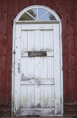 Ovessa kyltti PuuCee, Varjakansaaren vanhan sahakylän ulkohuussin ovi.