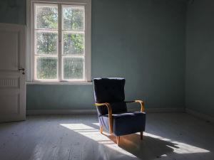 Sininen nojatuoli tyhjässä huoneessa, taustalla moniruutuinen vanha ikkuna, josta paistaa kesäinen aurinko.