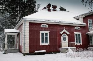 Varjakansaaren vanhan sahakylän päärakennus, punavalkoinen kaksikerroksinen puutalo kuvattuna talvella.