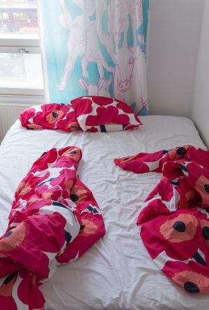 Sänky, jossa on rakastelun jäljiltä myllätyt unikkolakanat.