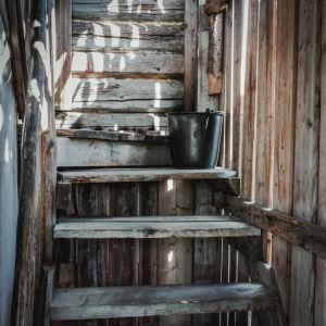 Saunan portaat, portailla musta saunaämpäri.